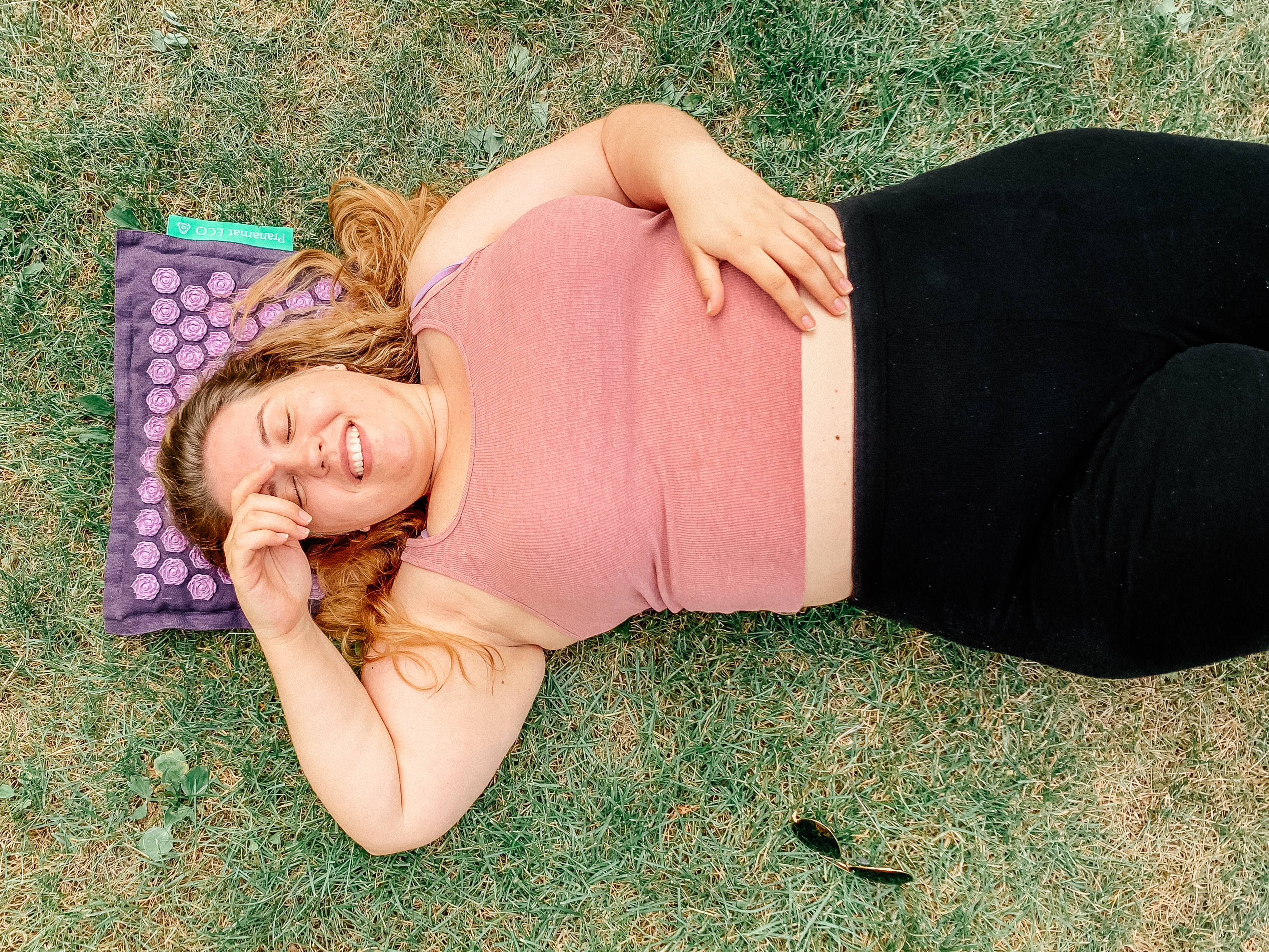 Uśmiechnięta kobieta leży na trawie. Mata do akupresury pranamat.