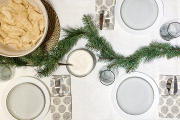 stół wigilijny, zielona girlanda, szare ściereczki, pierogi, sztućce, biały obrus