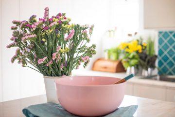Różowe kwiaty i duża miska na blacie w kuchni.