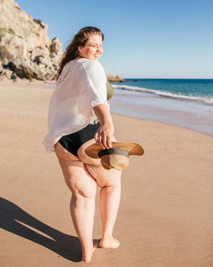 Kobieta na plaży w czarnym stroju kąpielowym i białej koszuli.